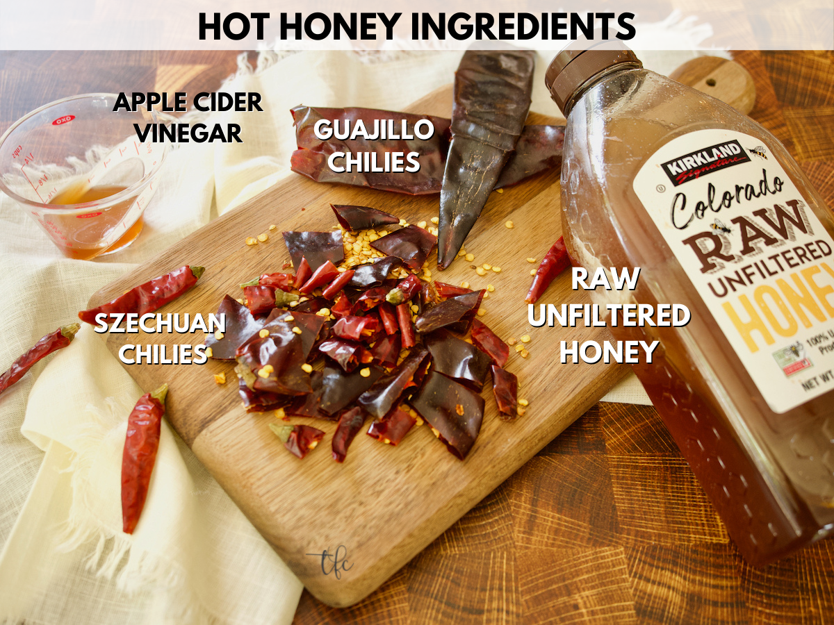 Ingredients for hot honey recipe with apple cider vinegar, chopped szechuan and guajillo chili peppers, and honey.