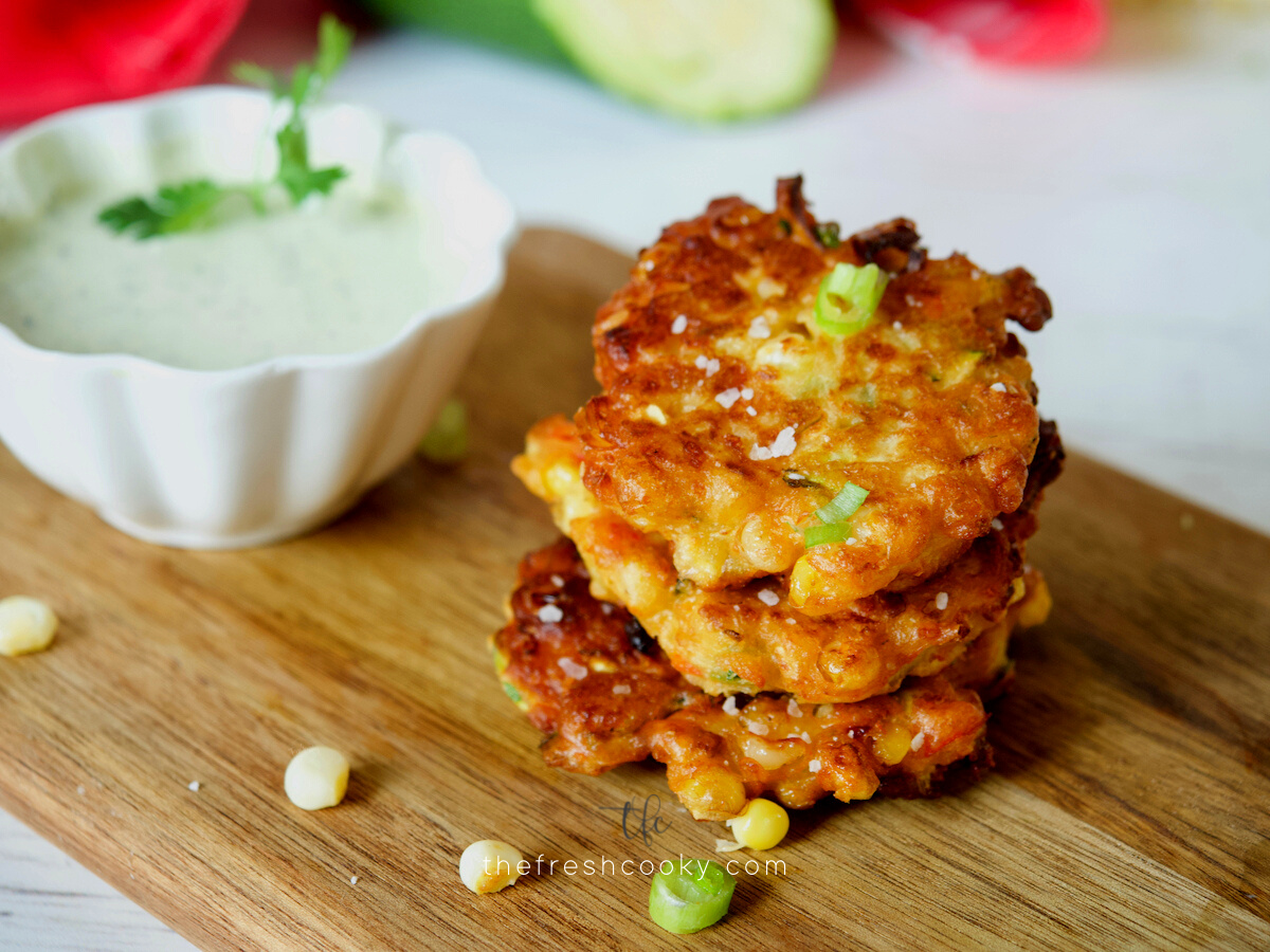 Delicious zucchini corn fritters stacked and sitting on a cutting board with some ranch dressing in a bowl behind.