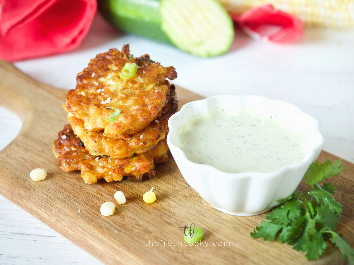 Zucchini Corn Fritters on cutting board with ranch dressing for dipping.