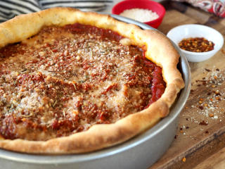 Chicago-Style Deep dish pizza in pan with condiments fresh out of the oven.