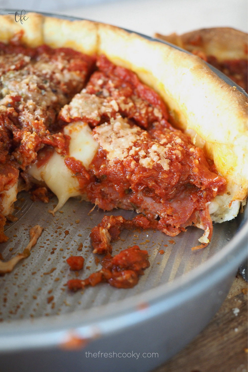 Chicago style deep dish pizza in pan with a slice removed and melting cheese and pepperoni oozing from slice.