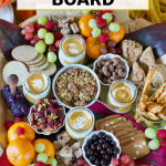 Long pin for easy Fall charcuterie board with beautiful wooden board filled with fall breakfast foods like yogurt, granola, fruit, crackers, nuts, nibbles, cheese and chocolate.