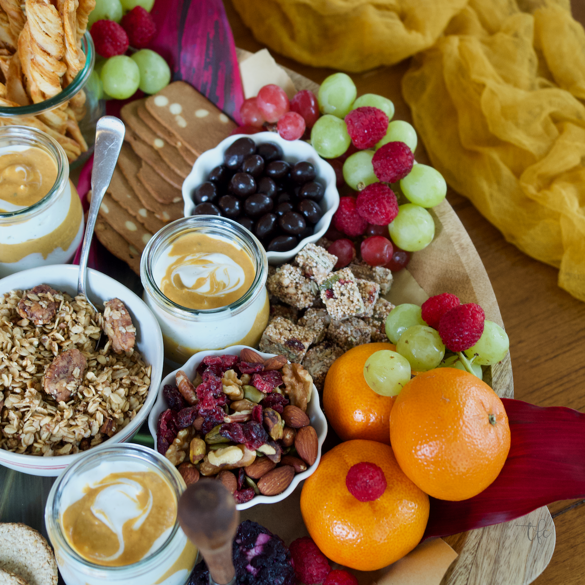 Fall Charcuterie Board with image of right half of board, highlighting the granola, oranges and fruit, trail mix and more.