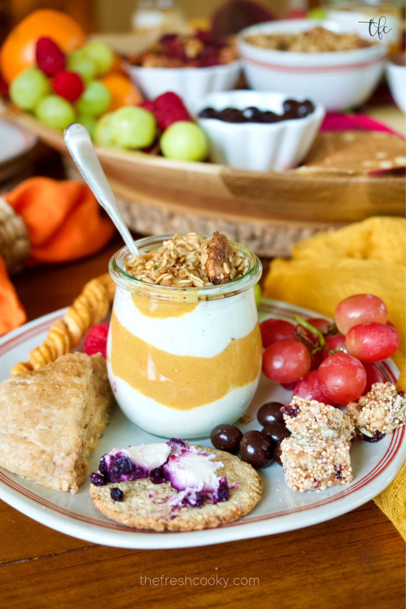 A plate filled with delicious pumpkin yogurt, cinnamon scones, cheese and crackers, grapes and other nibbles from the fall charcuterie breakfast board.