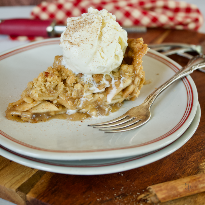 Slice of gluten-free apple pie on a plate with a fork and a scoop of melting vanilla ice cream on top.