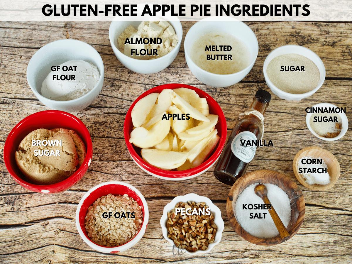 Ingredient shot for gluten-free apple pie L-R oat flour, almond flour, melted butter, sugar, cinnamon, cornstarch, salt, pecans, oats, brown sugar, apples and vanilla.