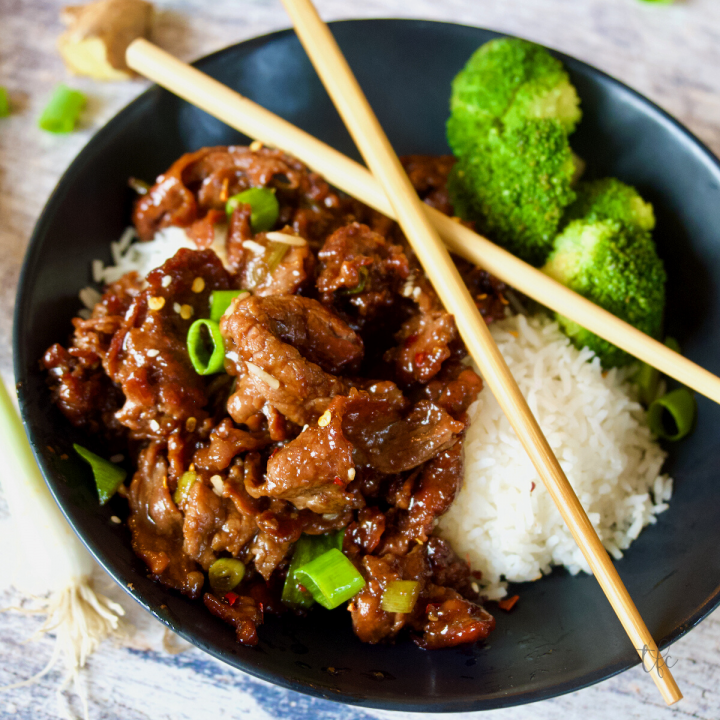 Mongolian Beef image of black bowl filled with Mongolian beef, rice and broccoli with chopsticks on top.