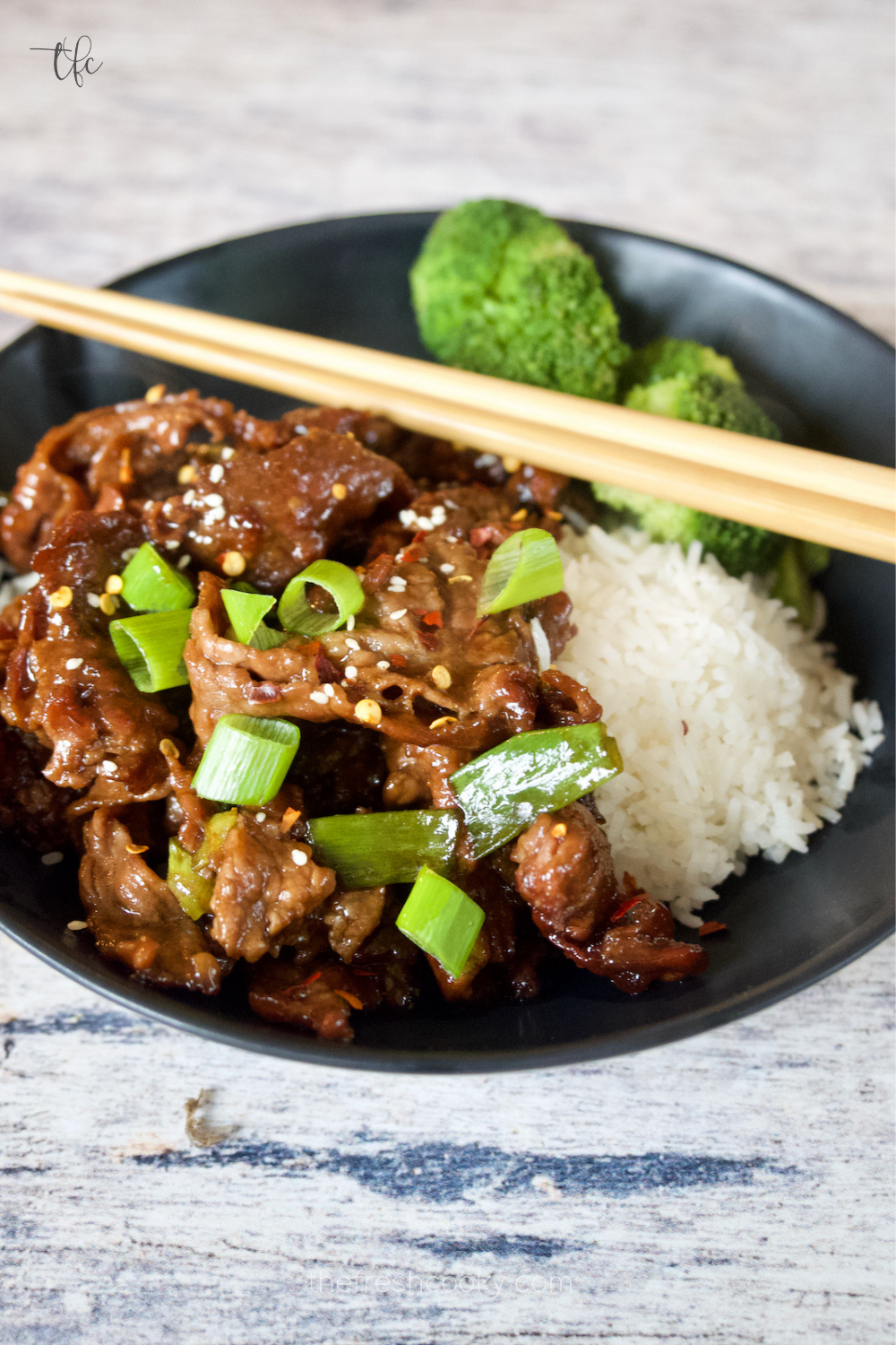 Mongolian Beef crispy and saucy in a black bowl with white rice and steamed broccoli.