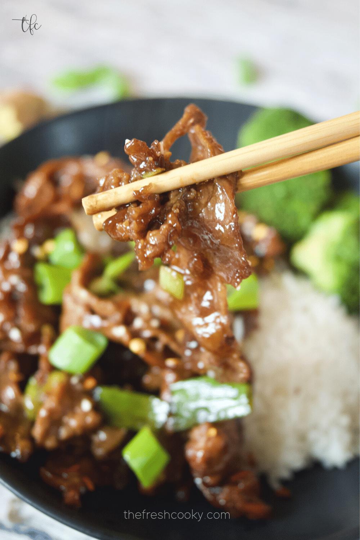 Grabbing a bite of tender Mongolian Beef with chopsticks.