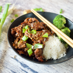 Facebook image for Mongolian Beef with Shaved steak in a bowl with green onions, white rice and steamed broccoli and chopsticks.
