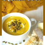 Copycat Panera Autumn Squash Soup pin with image of bowl of soup with pepitas and fresh french bread on the plate.