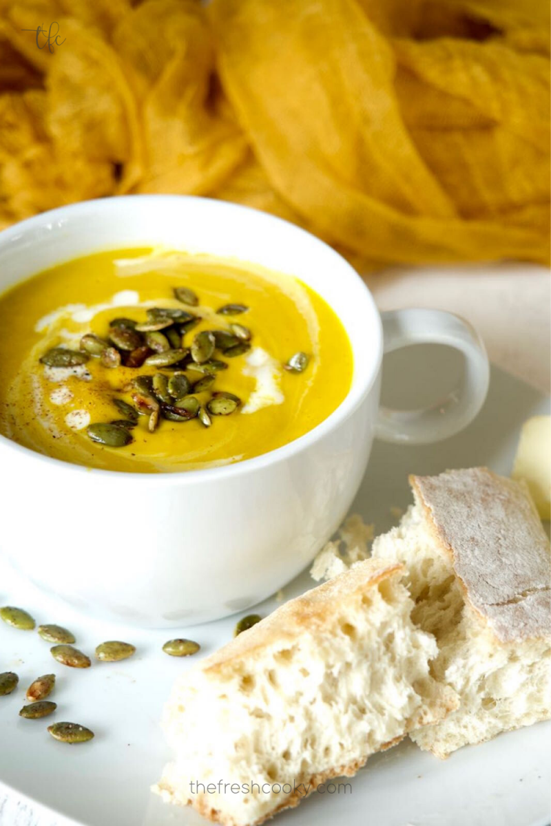 Autumn Squash Soup in pretty white two handled bowl with pepitas and french bread and butter.