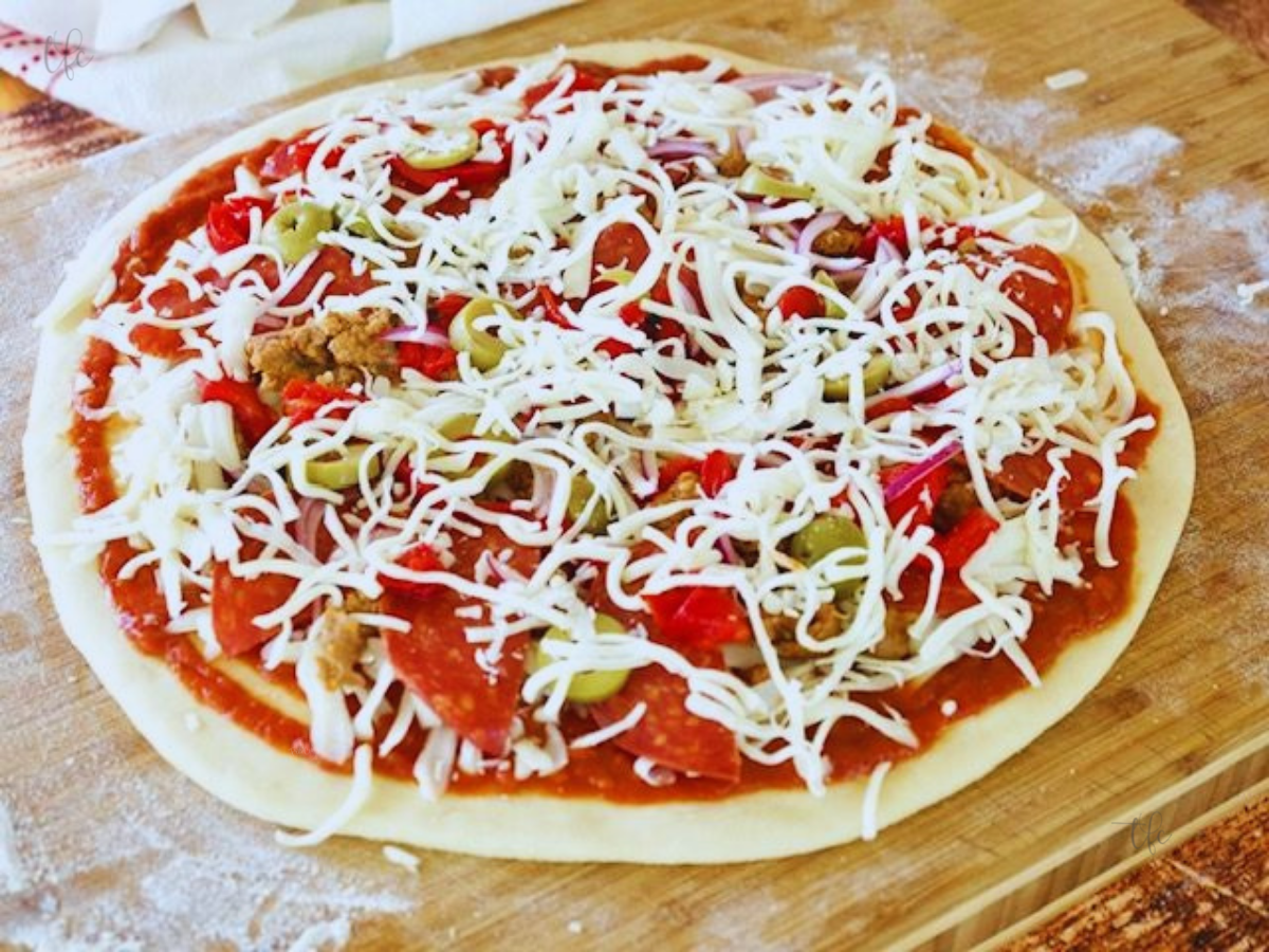 Image of pizza dough rolled out with sauce and toppings on top ready for the oven.