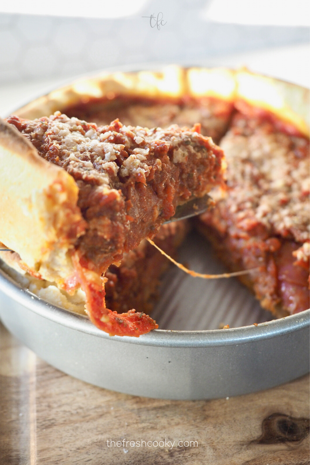 Pulling out slice of deep dish pan pizza.