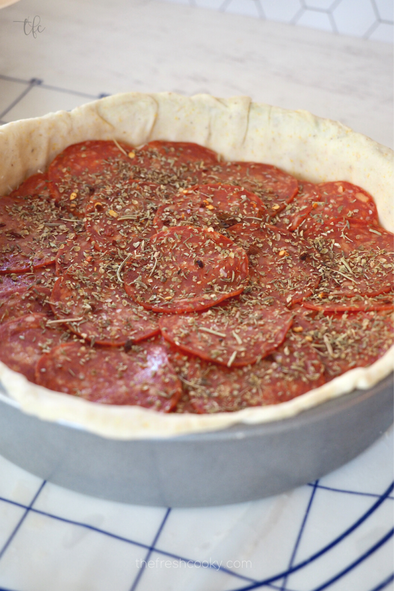 Layered toppings on top of cheese for deep dish pizza, here is used pepperoni and Italian seasoning.
