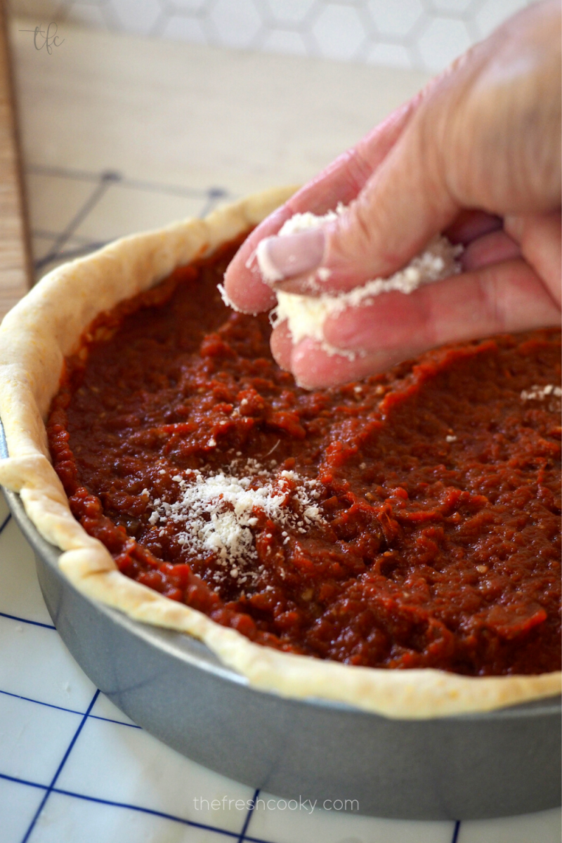 Sprinkling grated parmesan cheese on top of pizza sauce for deep dish pizza.