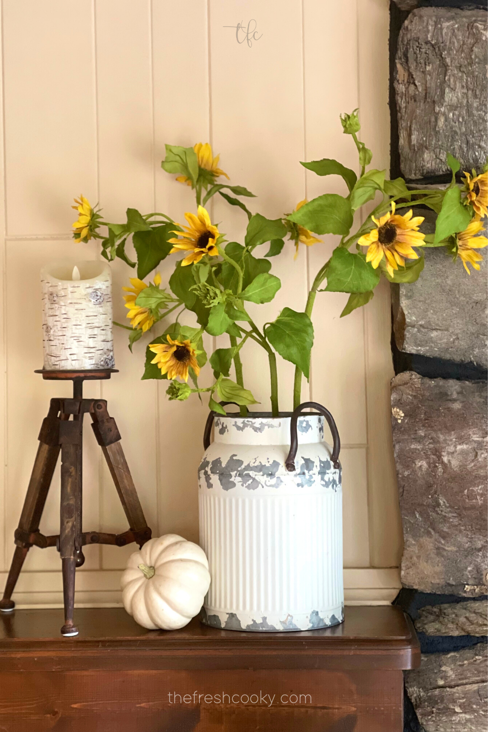 Fall mantle decor with milk can filled with pretty sunflowers and a candle and white pumpkin.