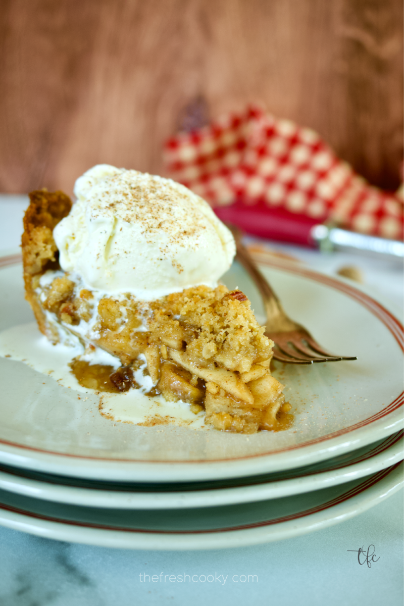 Slice of gluten-free apple pie ala mode on a plate with a fork nearby.