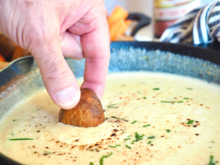 Easy Beer Cheese Dip with hand holding pretzel bite dipping into hot melty cheese dip.