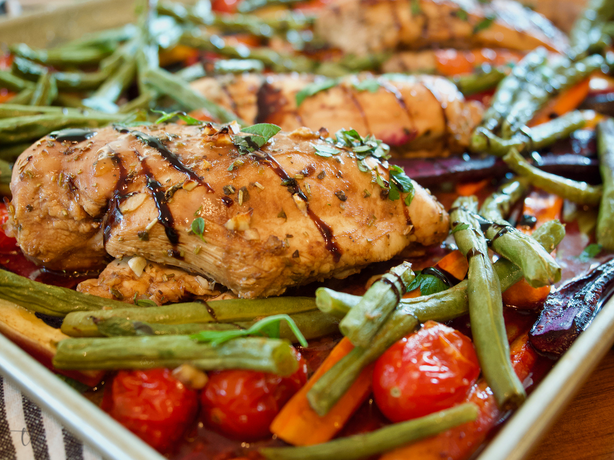 Horizontal image of baked chicken and veggies on sheet pan with balsamic glaze and marinade.